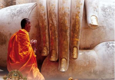Monge sentado em prece, frente a uma estátua gigantesca, onde aparece apenas a mão